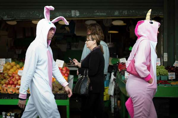 A bunny and a unicorn stroll through Pike Place Market during the 7th annual BunnyCon bar hop in in Seattle on Saturday, April 22, 2017. Hundreds of bunnies (and some carrots) hopped their way through a dozen downtown Seattle bars during the nearly 15 hour event.