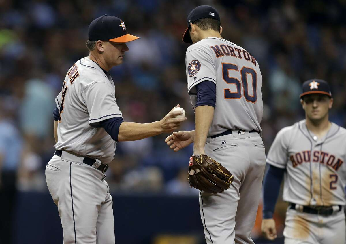 Houston Astros manager A.J. Hinch, left, takes the ball from starting pitcher Charlie Morton as Morton is taken out of the baseball game against the Tampa Bay Rays during the sixth inning Saturday, April 22, 2017, in St. Petersburg, Fla. (AP Photo/Chris O'Meara)