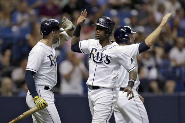 Tampa Bay Rays' Tim Beckham, center, celebrates with Shane Peterson, right, and Evan Longoria, left, after scoring on a two-run single by Peter Bourjos off Houston Astros relief pitcher Will Harris during the sixth inning of a baseball game Saturday, April 22, 2017, in St. Petersburg, Fla. (AP Photo/Chris O'Meara)