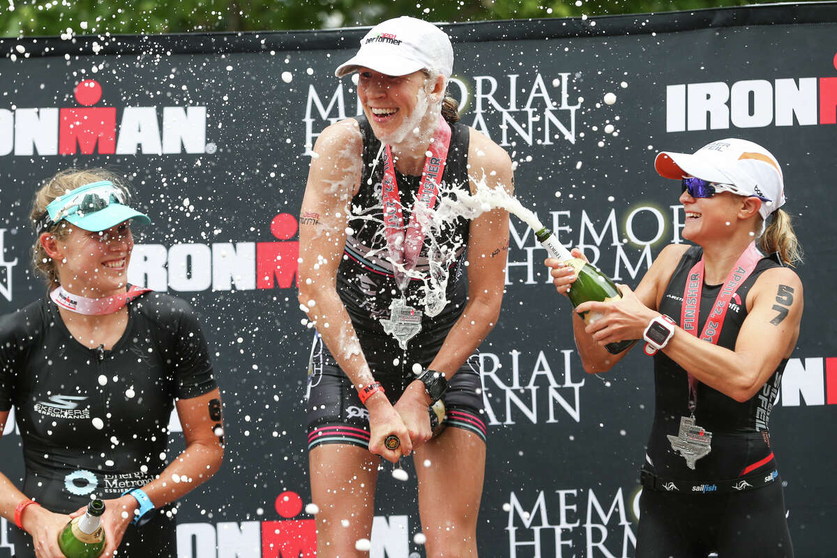 From the left: Maja Stage-Nielsen, of Denmark, Jodie Robertson, of New York, and Michaela Herlbauer, of Austria, pop champagne bottles at the awards podium during the Memorial Hermann IRONMAN North American Championship Texas on Saturday, April 22, 2017, in The Woodlands.