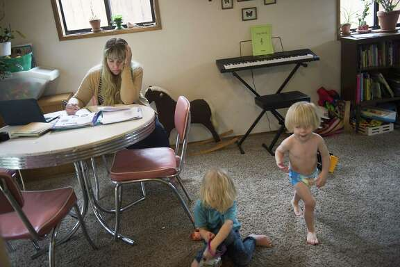 Jasmin Cross tries to study while her sons, Sebastian and Vyvyan, play in their home in Portland, Ore. Cross attends a community college and their father works full time, which she said they could not do without free child care through Head Start. Government spending on high-quality day care in early years delivers an economic boon that lasts three generations, research finds.