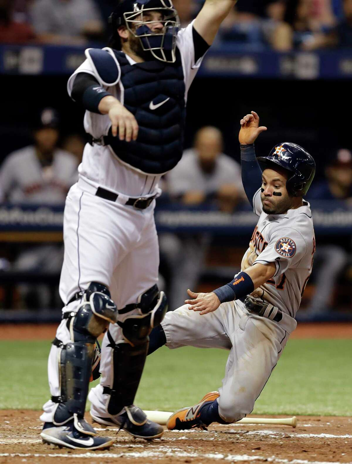 The Astros' Jose Altuve slides in under a high throw to Rays catcher Derek Norris on a grounder by Evan Gattis in the sixth inning. Altuve was 1-for-3 with his first home run of the season in Saturday's 6-3 loss.