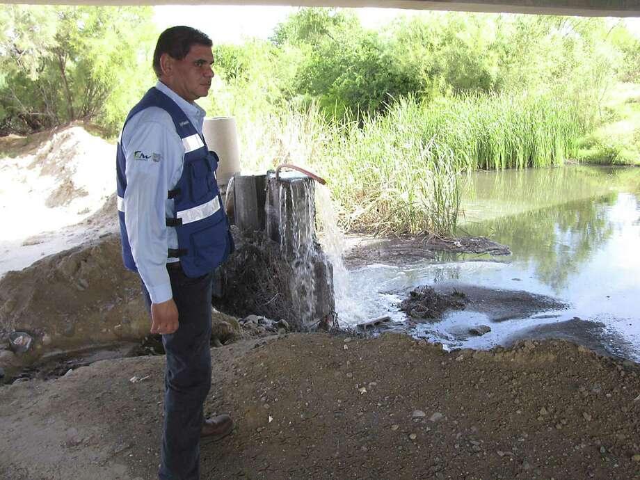 Javier Saavedra of Nuevo Laredo's COMPA water utility eyes sewage in a creek. Photo: Bill Lambrecht / San Antonio Express-News / San Antonio Express-News