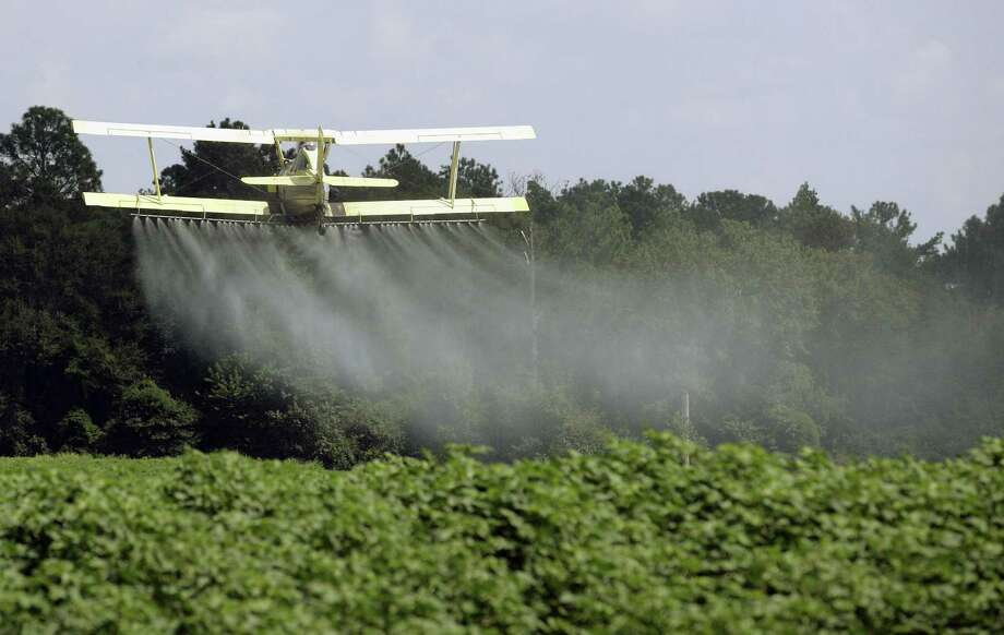 A crop duster sprays a field of crops just outside Headland, Ala. Dow Chemical is pushing the Trump administration to scrap the findings of federal scientists who point to a family of widely used pesticides as harmful to about 1,800 critically threatened or endangered species. Photo: Dave Martin /Associated Press / Stratford Booster Club