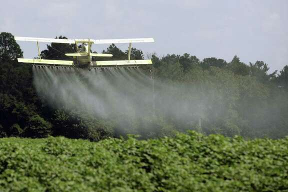 A crop duster sprays a field of crops just outside Headland, Ala. Dow Chemical is pushing the Trump administration to scrap the findings of federal scientists who point to a family of widely used pesticides as harmful to about 1,800 critically threatened or endangered species.