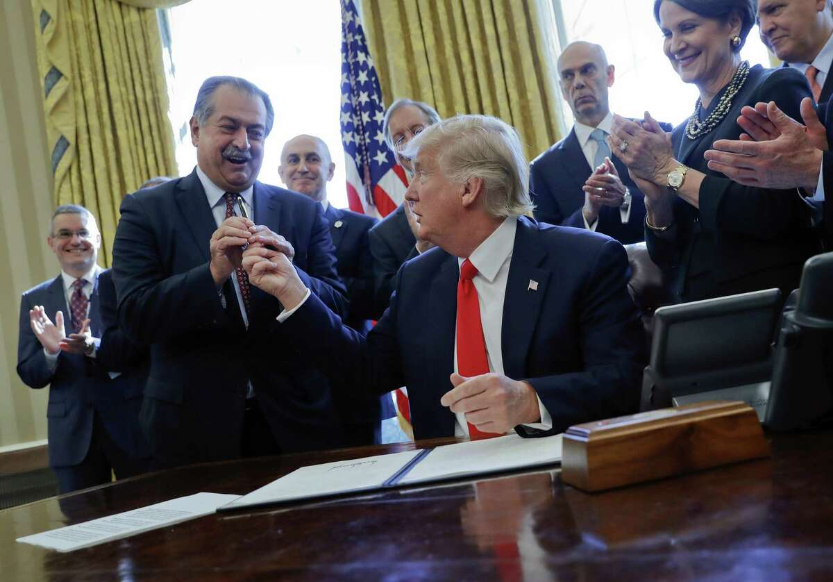President Donald Trump gives the pen he used to sign an executive order to Dow Chemical Chairman and CEO Andrew Liveris as other business leaders applaud in the Oval Office of the White House in Washington.