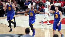 Golden State Warriors' JaVale McGee, Andre Iguodala and Klay Thompson celebrate an Iguodala basket in 4th quarter of 119-113 win over Portland Trail Blazers in Game 3 of NBA Western Conference 1st Round Playoffs at Moda Center in Portland, Oregon on Saturday, April 22, 2017.