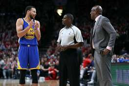 Golden State Warriors' Stephen Curry and Mike Brown confer with official in 3rd quarter of Warriors' 119-113 win over Portland Trail Blazers in Game 3 of NBA Western Conference 1st Round Playoffs at Moda Center in Portland, Oregon on Saturday, April 22, 2017.