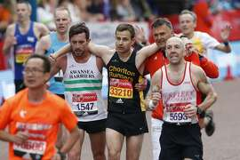 A runner is helped near the finish line during the London marathon on April 23, 2017 in London. / AFP PHOTO / Adrian DENNISADRIAN DENNIS/AFP/Getty Images