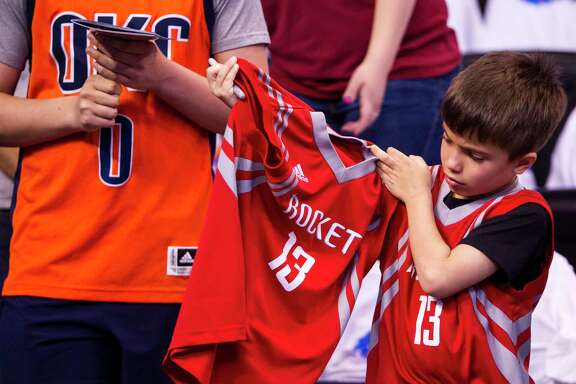 Houston Rockets fan Christian Frost checks a jersey he is having autographed before Game 4 of the NBA Western Conference first-round playoff series at Chesapeake Energy Arena on Sunday, April 23, 2017, in Oklahoma City.