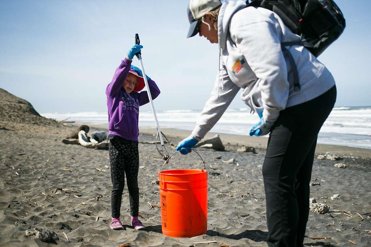 Ellen Ashley holds the bucket as Grace Coachman, 6, picks up a water bottle during the Surfrider Foundation's annual beach clean-up event at Ocean Beach in San Francisco, Calif. Sunday, April 23, 2017.