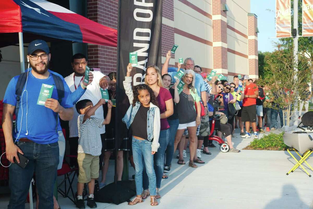 Weekend opening events at Dick's Sporting Goods at 11200 Broadway Street in Pearland had crowds lined outside the door eager to see the new store, get a chance to win prizes and get autographs from sports stars Andre Johnson and Robert Horry. Customers, above, show off gift cards offering them a chance to claim the price in the gift safe on Apr. 21.