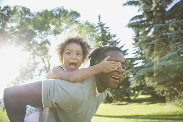 Portrait of playful girl covering fathers eyes in park