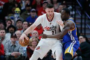 PORTLAND, OR - APRIL 22:  Jusuf Nurkic #21 of the Portland Trail Blazers is guarded by Draymond Green #23 of the Golden State Warriors during Game Three of the Western Conference Quarterfinals of  the 2017 NBA Playoffs at Moda Center on April 22, 2017 in Portland, Oregon.  NOTE TO USER: User expressly acknowledges and agrees that, by downloading and or using this photograph, User is consenting to the terms and conditions of the Getty Images License Agreement.  (Photo by Jonathan Ferrey/Getty Images)