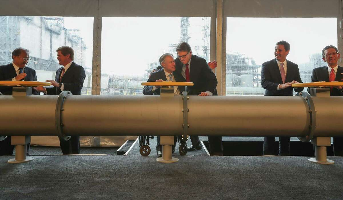 Texas Govenor Greg Abbott and New Department of Energy Secretary Rick Perry hug after a ceremonial valve opening Thursday, April 13, 2017, in Richmond. NRG Energy celebrates the official opening of its Petra Nova carbon capture plant--which captures carbon from a coal-fired power plant. Technically the plant has been operational since late last year. Plant is the largest of its kind in the world. ( Steve Gonzales / Houston Chronicle )