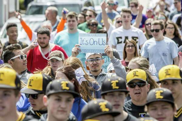 """Cam Koizumi, an Omega Psi student from the University of New Haven holds a sign reading, """"It's On Us."""" referring to the role men need to play in preventing sexual violence he said. The Rape Crisis Center of Milford held a Walk A Mile In Her Shoes event in downtown Milford, Conn. on Sunday, April 23, 2017. The annual walk is held to raise awareness around issues of rape, sexual assault and gender violence."""