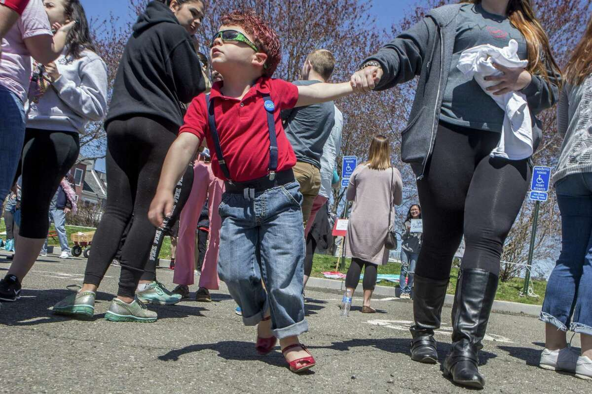 Stephanie Dezenzo, walks with her son, Nathan Dezenzo, 4, at Lisman Landing in Milford, Conn. He is wearing ladies shoes in accordance with the playful rules of the Walk A Mile In Her Shoes event held by The Rape Crisis Center of Milford. The event was held on Sunday, April 23, 2017. The annual walk is held to raise awareness around issues of rape, sexual assault and gender violence.