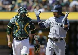 Seattle Mariners' Taylor Motter, right, celebrates after hitting a grand slam off Oakland Athletics' Andrew Triggs in the third inning of a baseball game Sunday, April 23, 2017, in Oakland, Calif. At left is A's catcher Stephen Vogt. (AP Photo/Ben Margot)