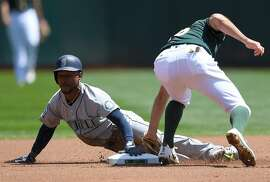 OAKLAND, CA - APRIL 23:  Jarrod Dyson #1 of the Seattle Mariners steals second base sliding in before the tag of Adam Rosales #16 of the Oakland Athletics in the top of the first inning at Oakland Alameda Coliseum on April 23, 2017 in Oakland, California.  (Photo by Thearon W. Henderson/Getty Images)