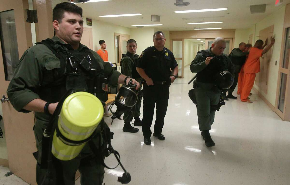 Bexar County Sheriff's Office (BCSO) deputy Daniel Pollard (left) holds a mask and air tank used in emergency situations in the Bexar County Jail in 2017. County officials are worried about overtime and staff turnover that has plagued the facility for more than a decade.