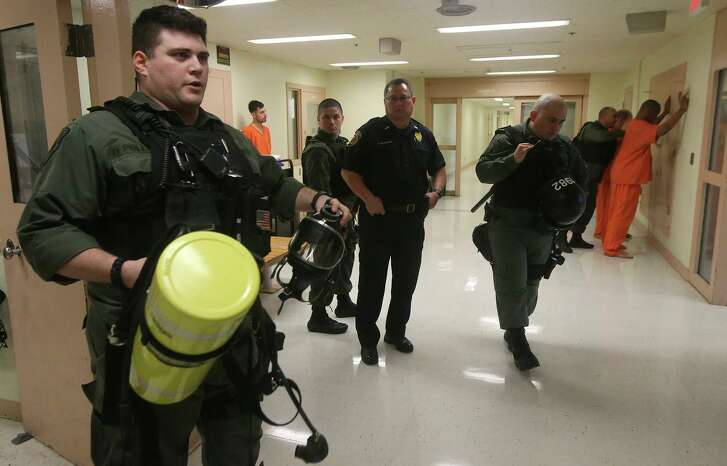 ABOVE: Bexar County Sheriff's Office (BCSO) deputy Daniel Pollard (left) holds a mask and air tank used in emergency situations in the Bexar County Adult Detention Center. Pollard is a member of a special unit in the BCSO called S.E.R.T. or Special Emergency Reponse Team that uses specially trained deputies to handle high risk situations that are outside of the scope of regular detention officers' duties. The unit is trained to fight fires, respond to escape attempts, quell riots, and subdue violent inmates.