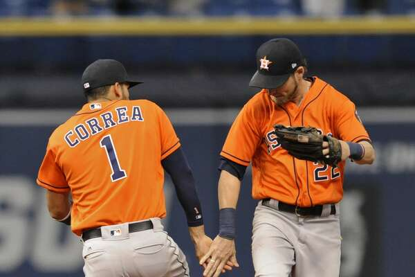 Houston Astros' Carlos Correa (1) and Josh Reddick (22) celebrate a 6-4 win over the Tampa Bay Rays during the 10th inning of a baseball game, Sunday, April 23, 2017 in St. Petersburg, Fla. (AP Photo/Steve Nesius)