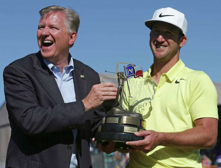 Kevin Chappell is handed the trophy by Valero's Gary Simmons after the final round of the Valero Texas Open at TPC San Antonio Oaks Course on April 23, 2017.