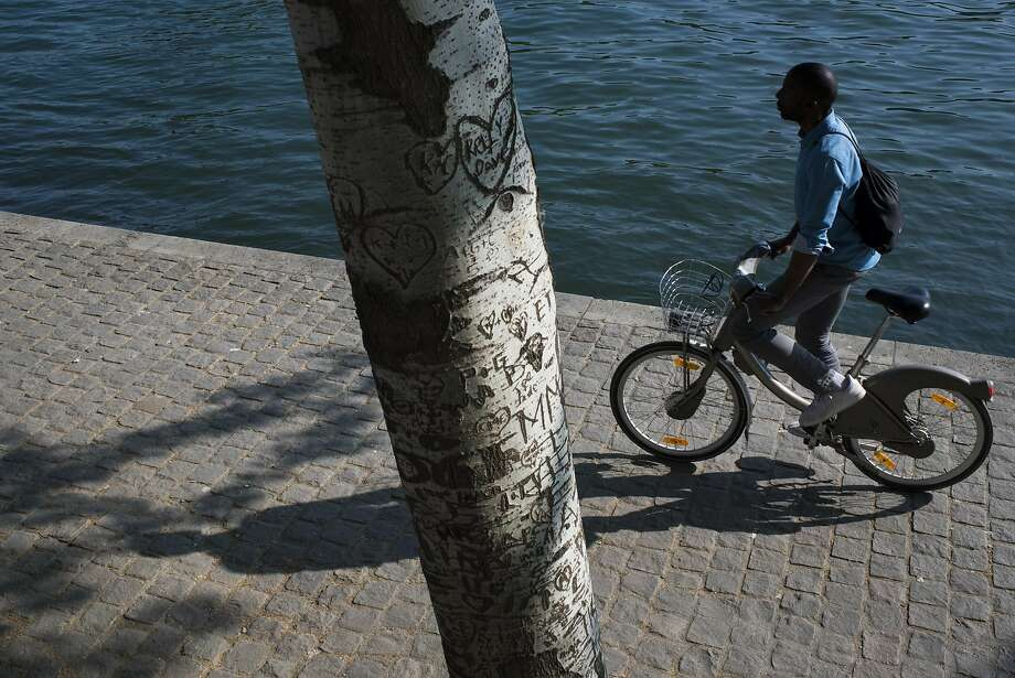 A Velib cyclist rides on Quai des Tuileries in Paris. Popular with Parisians and tourists alike, Velib is a bike sharing program consisting of over 23,000 bicycles and 1,800 rental/return stations. Photo: Pete Kiehart, Special To The Chronicle