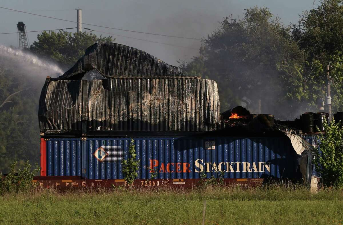 HFD firefighters working on to put off fire from a shipping container on the railroad near Conti and Chapman Streets Sunday, April 23, in Houston.