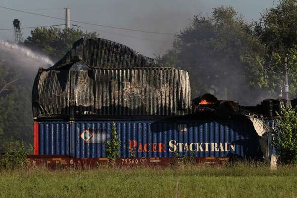 HPD firefighters working on to put off fire from a shipping container on the railroad near Conti and Chapman Streets Sunday, April 23, in Houston.