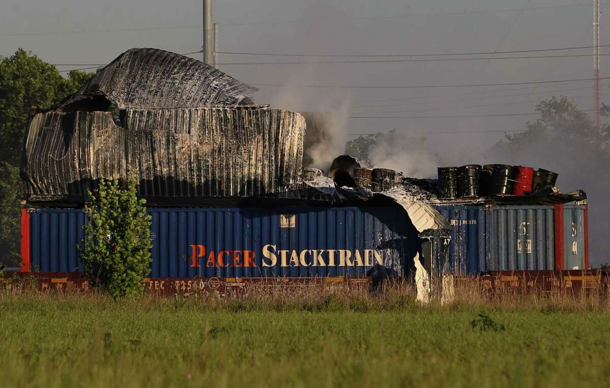 HFD firefighters working on to put off fire from a shipping container on the railroad near Conti and Chapman Streets Sunday, April 23, in Houston. The items inside the shopping container are visible after the metal walls fell apart.