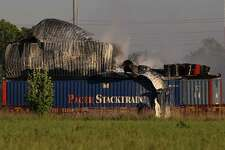 HPD firefighters working on to put off fire from a shipping container on the railroad near Conti and Chapman Streets Sunday, April 23, in Houston. The items inside the shopping container are visible after the metal walls fell apart.