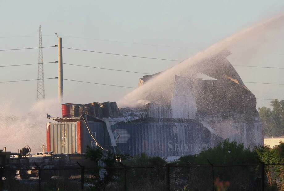 HPD firefighters working on to put off fire from a shipping container on the railroad near Conti and Chapman Streets Sunday, April 23, in Houston. The items inside the shopping container are visible after the metal walls fell apart. Photo: Yi-Chin Lee / Houston Chronicle, Yi-Chin Lee / Houston Chronicle 2017