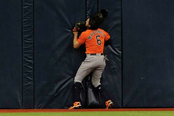 Astros center fielder Jake Marisnick gets some face time, left, with the wall at Tropicana Field on a first-inning catch. At right, trainer Jeremiah Randall goes to check on Marisnick, flanked by Josh Reddick (22).