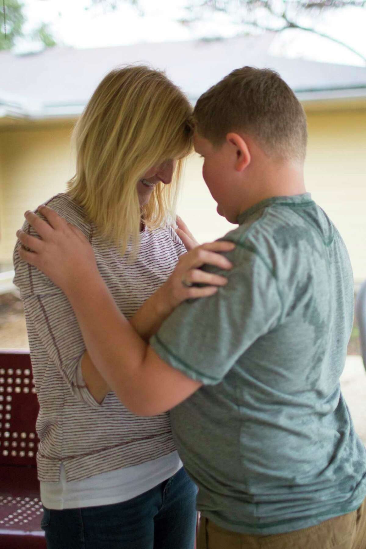 Julie Mele and her 12-year-old son share a moment in the backyard of their home at Fort Hood in Killeen, where her husband was stationed.