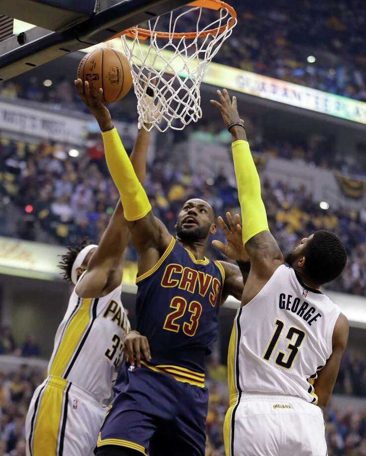 Cleveland Cavaliers' LeBron James (23) shoots against Indiana Pacers' Paul George (13) and Myles Turner during the first half in Game 4 of a first-round NBA basketball playoff series, Sunday, April 23, 2017, in Indianapolis. (AP Photo/Darron Cummings) ORG XMIT: NAF112 Photo: Darron Cummings / Copyright 2017 The Associated Press. All rights reserved.