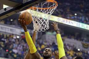 Cleveland Cavaliers' LeBron James (23) shoots against Indiana Pacers' Paul George (13) and Myles Turner during the first half in Game 4 of a first-round NBA basketball playoff series, Sunday, April 23, 2017, in Indianapolis. (AP Photo/Darron Cummings) ORG XMIT: NAF112