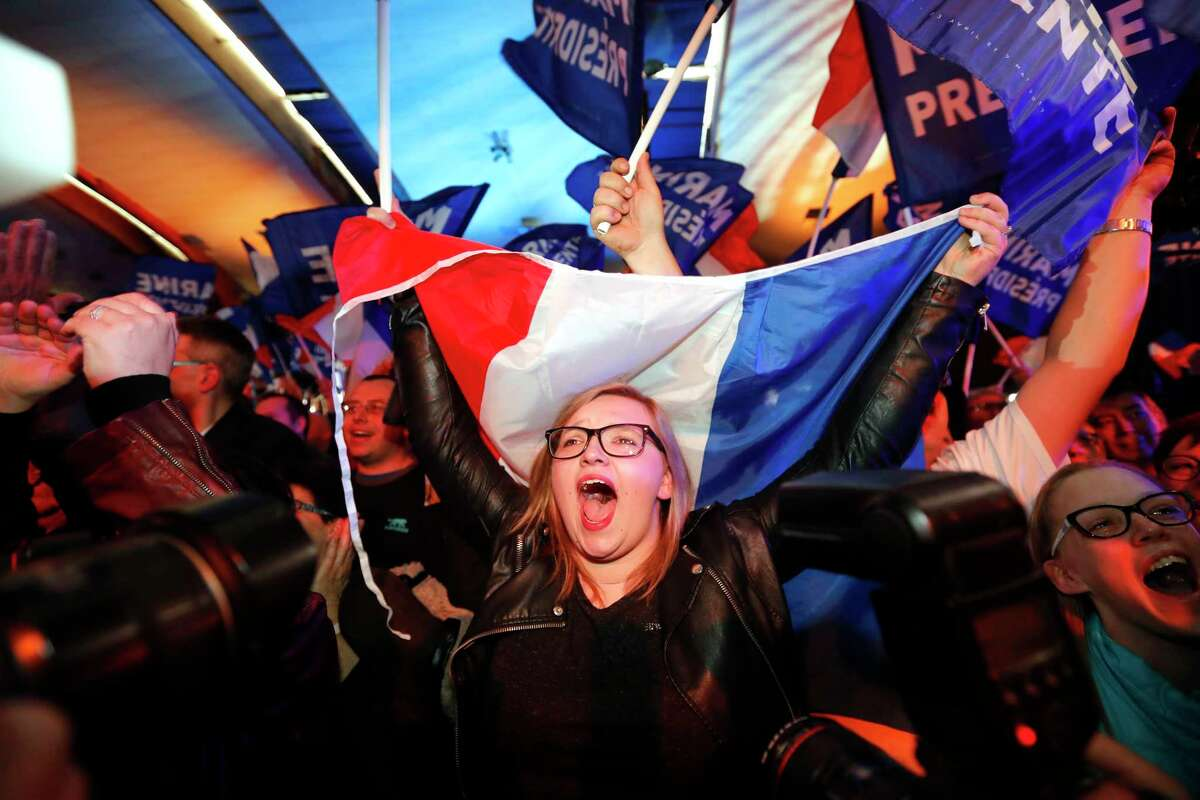 Supporters of Marine Le Pen celebrate after results of the first round of the election are announced.
