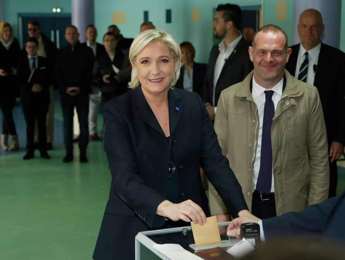 Marine Le Pen casts her vote for the first-round presidential election while National Front Henin-Beaumont's mayor Steeve Briois, right, looks on.
