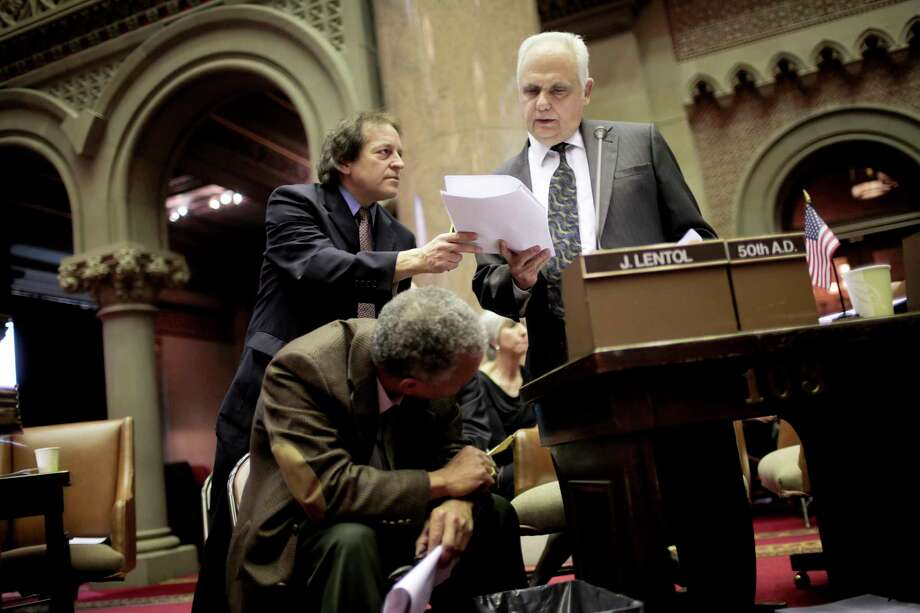 New York State Assemblyman Joseph Lentol, right, answers questions during a debate about gun control legislation in Albany, N.Y., Jan. 15, 2013. The New York State Assembly debated and prepared to vote Tuesday on a package of gun measures that would significantly expand the state's ban on assault weapons. (Nathaniel Brooks/The New York Times) Photo: NATHANIEL BROOKS / NYTNS