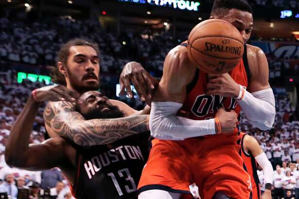 With OKC teammate Steven Adams using some strong-arm tactics on the Rockets' James Harden, Thunder guard Russell Westbrook pulls down one of the 14 rebounds that were part of his third straight triple-double.