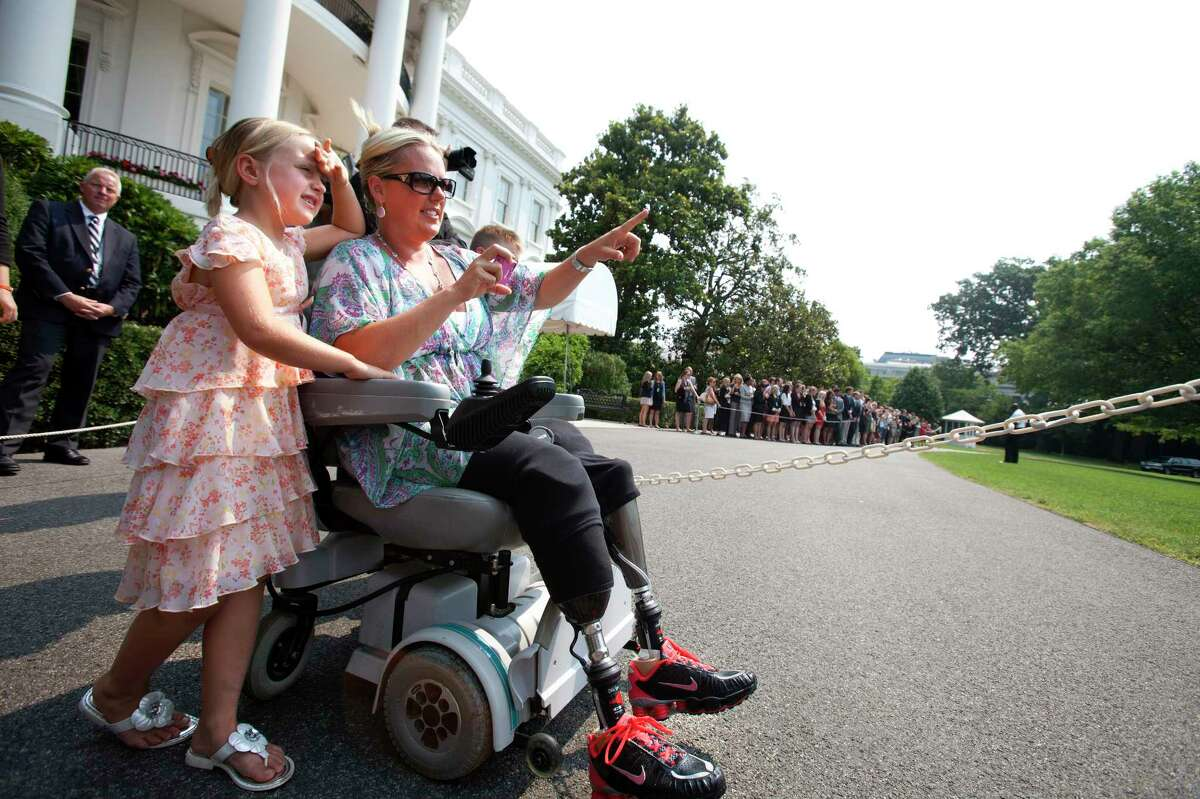 Stephanie Decker and her daughter Reese, 6, wave to President Barack Obama as he leaves the White House in Washington, Friday, June 29, 2012, via Marine One, in Washington. The Deckers now live in Sellersburg, Ind., and survived a tornado in Henryville, Ind. in March of 2012, during which the mother of two lost her legs while protecting her children from the storm. (AP Photo/Jacquelyn Martin)