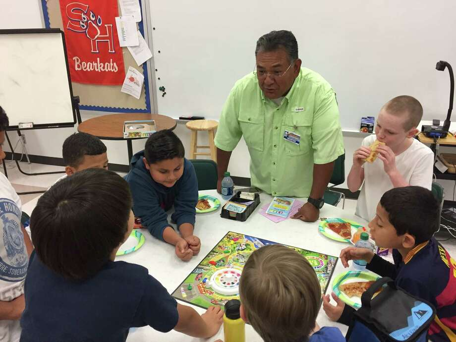 Lion Pete Martinez of the Conroe Noon Lions Club supervises a game of 'Life' with a group of 3rd graders during their FUN FRIDAY event at the club's adopted school of Reaves Elementary. Photo: Submitted Photo