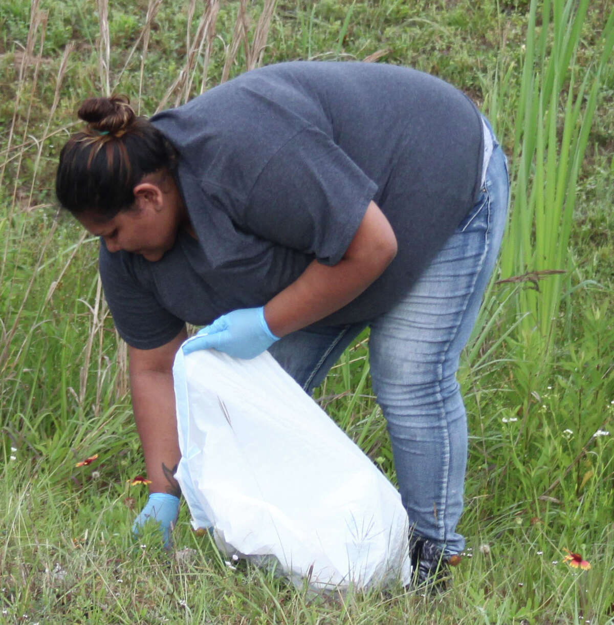Nohemi Gonzalez tidies up Liberty St in Shepherd, Texas as part of the Clean Up Shepherd event held on Earth Day April 22.