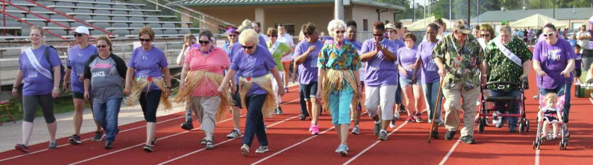 Cancer survivors kick off the North Liberty County Relay for Life event by walking the first lap around the track.