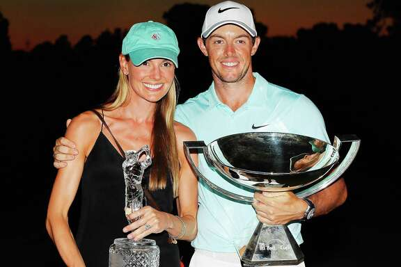 Rory McIlroy of Northern Ireland poses alongside Erica Stoll as they hold the FedExCup and Tour Championship trophies at East Lake Golf Club on Sept. 25, 2016 in Atlanta.