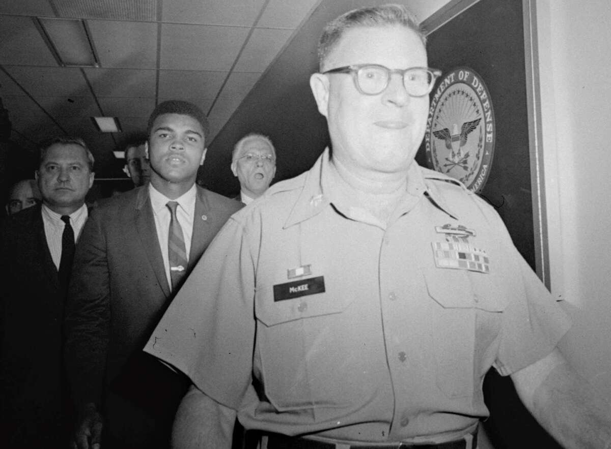Heavyweight champion Muhammad Ali is pictured being escorted from the Armed Forces Examining and Entrance Station in Houston, Texas, April 28, 1967, by Lt. Col. J. Edwin McKee, commandant of the station, after Ali refused Army induction. In refusing to accept the draft, Ali was forced out of boxing at the height of his career.