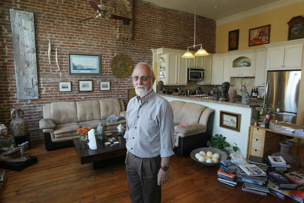 Retired UTMB researcher Ulli Budelmann stands in his living room, surrounded by his art and other collections.