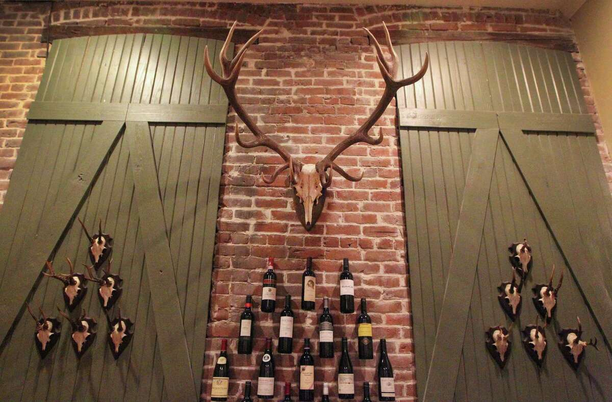 Deer skulls with antlers decorate the covered-up windows in Ulli Budelmann's Galveston home. The center wine rack was cleverly devised by putting small nails into grout, then wrapping picture wire around the wine bottlenecks, finishing with a loop. The loops go over the nails and your wine bottles appear to float on the wall's surface.