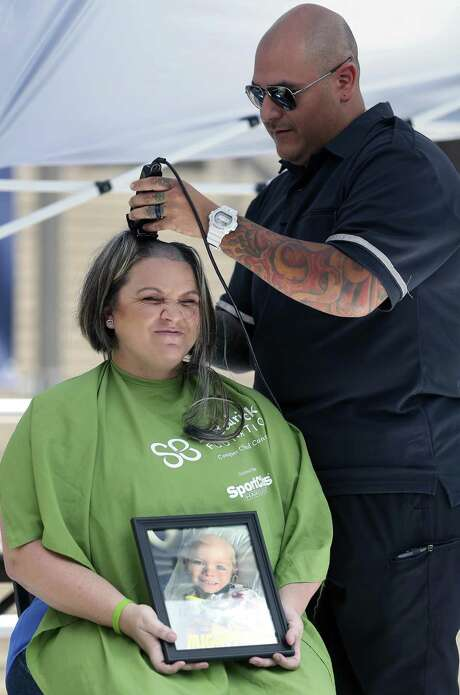 Chloe Herrera gets her hair shaved Tuesday, April 18, 2017 on the UTSA campus by her husband, Ted, during a fundraiser sponsored by Honors College students at UTSA for the St. Baldrick's Foundaiton, which supports cancer research. Herrera was the top fundraiser for the event. Photo: William Luther, Staff / San Antonio Express-News / © 2017 San Antonio Express-News
